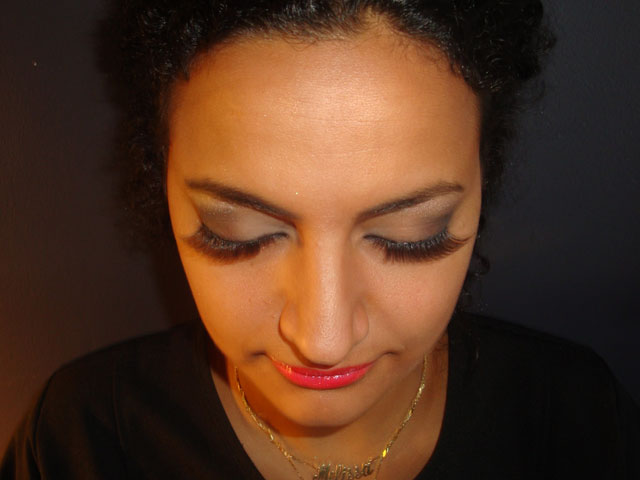 Makeup on woman with curly black hair, front view with eyes closed