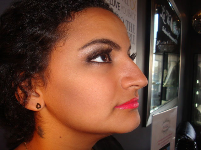 Makeup on woman with curly black hair, profile view