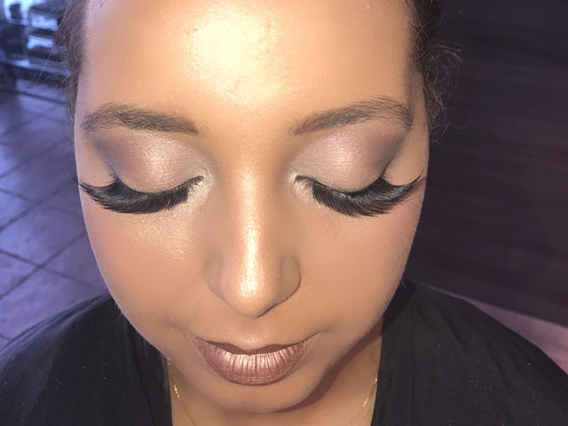 Makeup on woman with hair tied back and closed eyes